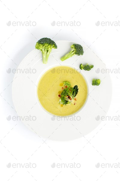 White plate with cream of broccoli soup, served with pine nuts o
