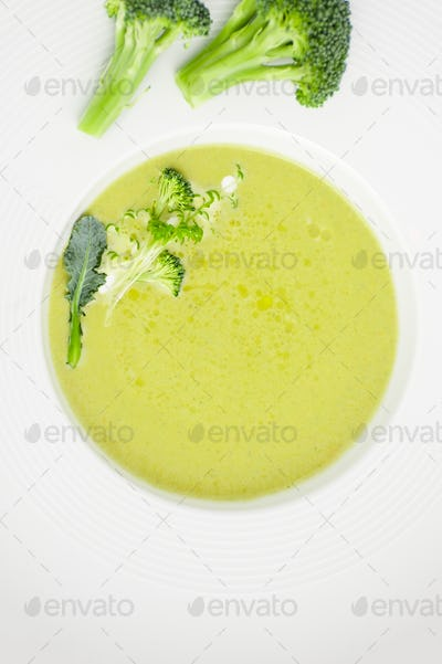 Cream of broccoli soup close-up in a white plate.