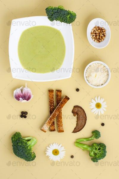 Cream soup of broccoli in a white plate and ingredients on a yel