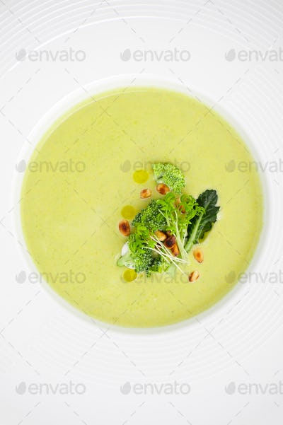 Cream of broccoli soup, served with pine nuts close-up in a whit