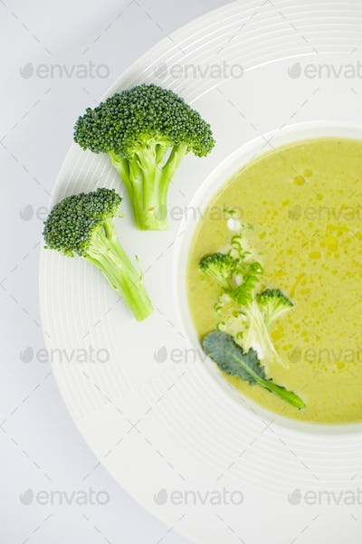 Cream of soup and inflorescences of broccoli close-up in a white