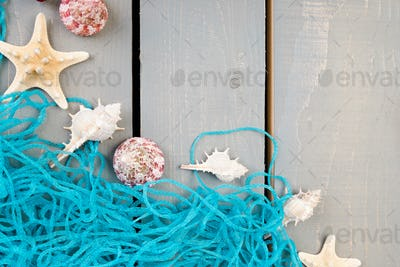 Seashells with blue net on grey wooden background. Flat lay.