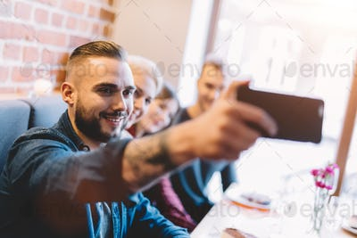 Young man taking a selfie with friends.