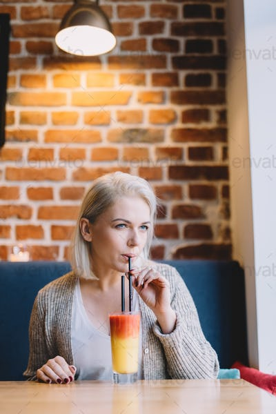 Young woman drinking colorful cocktail.
