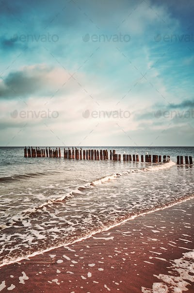 Vintage toned picture of an old wooden breakwater on a beach.