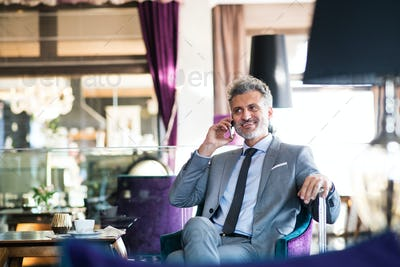 Mature businessman with smartphone in a hotel lounge.
