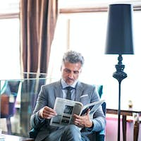 Mature businessman reading newspapers in a hotel lounge.