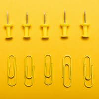 Yellow thumbtacks and clips over a yellow background