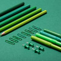 Colourful pencils, thumbtacks and clips over a green background