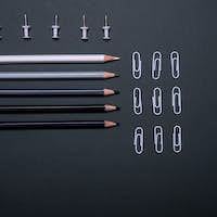 Colourful pencils, thumbtacks and clips over a black background