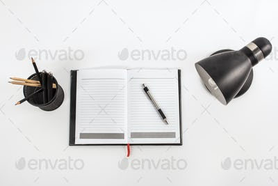 notebook, table lamp, and stationary at working space