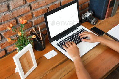 hands typing on laptop with wooden table at working space