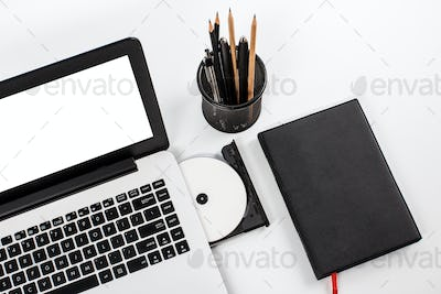 working space with laptop, disc, notebook and stationary