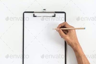 hand holding pencil and letterhead on clipboard
