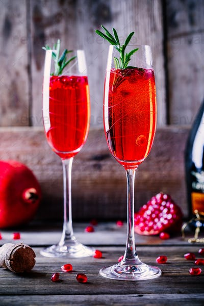Pomegranate champagne mimosa cocktail with rosemary