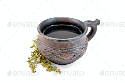 Tea with wormwood in clay cup