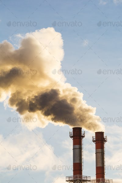 Stream of dark smoke from the chimney of factory