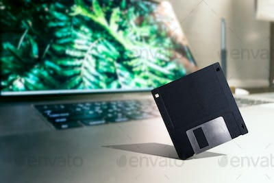 Old tech Floppy disk placed on Modern laptop