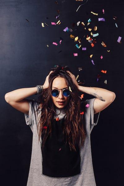 Adorable girl having fun with confetti