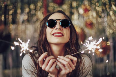 Beautiful girl holding sparklers in hands