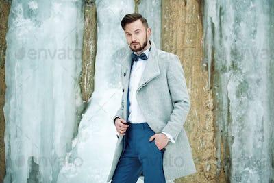 Outdoor portrait of handsome man in gray coat
