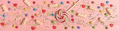 Colorful candies on pink background, top view