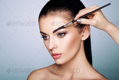 Beautiful brunette woman paints the eyebrows