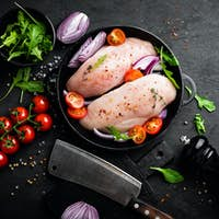 Fresh raw chicken meat, fillet marinated with spices, onion and tomatoes on black background