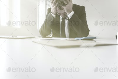 Despairing businessman with his head in his hands
