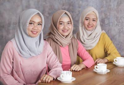 three beautiful muslim woman having a coffee time together