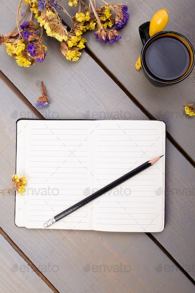Coffee cup and notebook on wooden table. Good morning .
