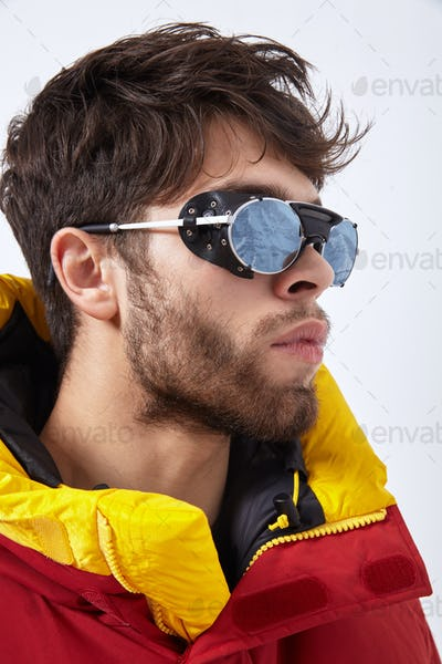 Portrait of mountaineer in winter clothes and ultraviolet protected sunglasses