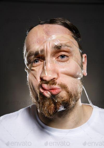 Studio portrait of funny scotch taped man face
