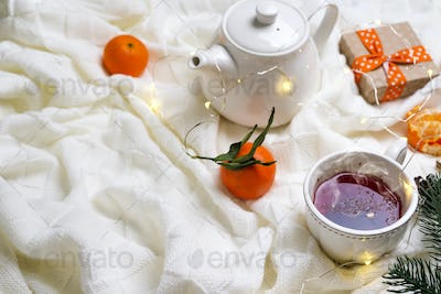 Hot Cup of tea with tangerines and sweaters on bed