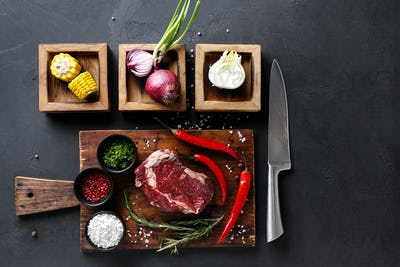 Rib eye steak with spices on wooden desk and diverse cooking ingredients in wooden boxes.