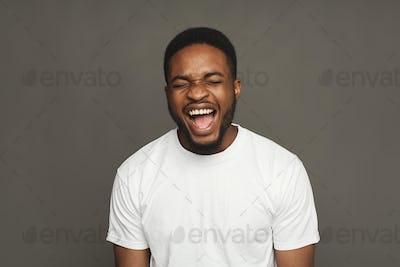 Black man expressing anger, feeling furious, shouting