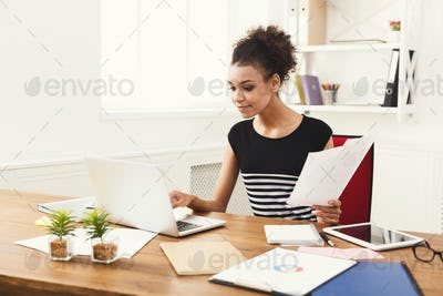 Business woman reading document at office desktop