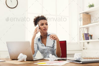 Serious angry business woman at work talking on phone