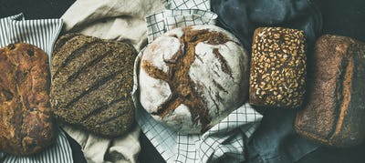 Flat-lay of Various bread selection loaves, black background