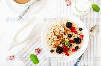 Tasty and healthy oatmeal porridge with berry, flax seeds and nuts