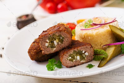 Zrazy cutlets with minced meat with pickled cucumber and eggs and garnish of bulgur
