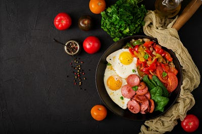 Breakfast. Fried eggs with sausage and vegetables in a frying pan