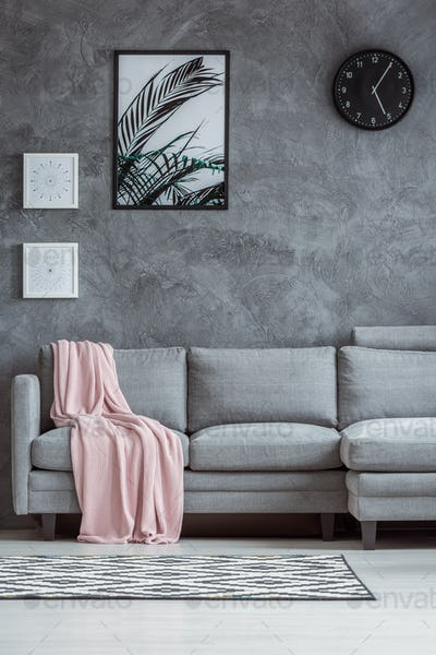 Concrete textured wall, gray couch