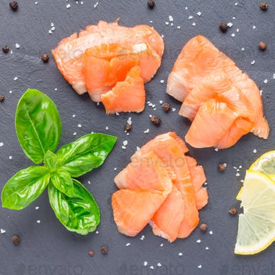 Smoked salmon filet with lemon and basil on gray stone, top view, square format