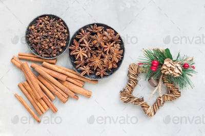 Aromatic winter spices in bowls, christmas decoration on background, top view, horizontal