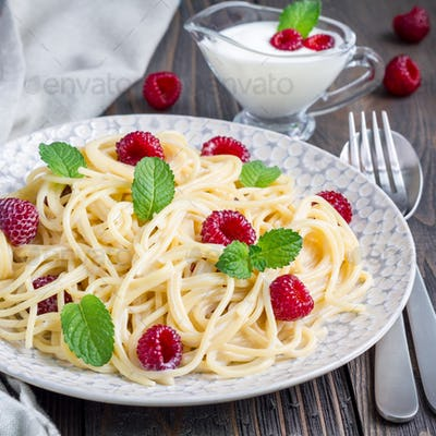 Spaghetti with sour cream, honey and raspberries, vegetarian, on gray plate, square format