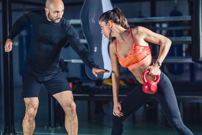 Personal trainer exercising with kettlebell with woman in the gy