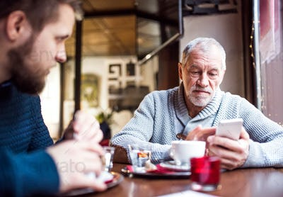 Senior father with smartphone and young son in a cafe.