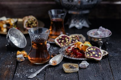 Turkish tea with authentic glass cups. Two cups of turkish tea and sweets on dark wood background