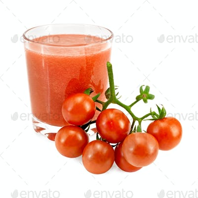 Juice tomato in a glass and a bunch of tomatoes